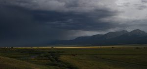 Fine art photo of rainstorm near the Wet Mountain range in Colorado. There is a thin strip of sunlight highlighting the scene inbright yellow with lots of grey and blue and dark dark yellowgreen